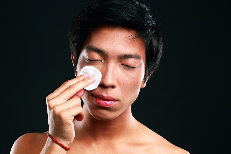 Asian man wipes his face with cotton pad on black background