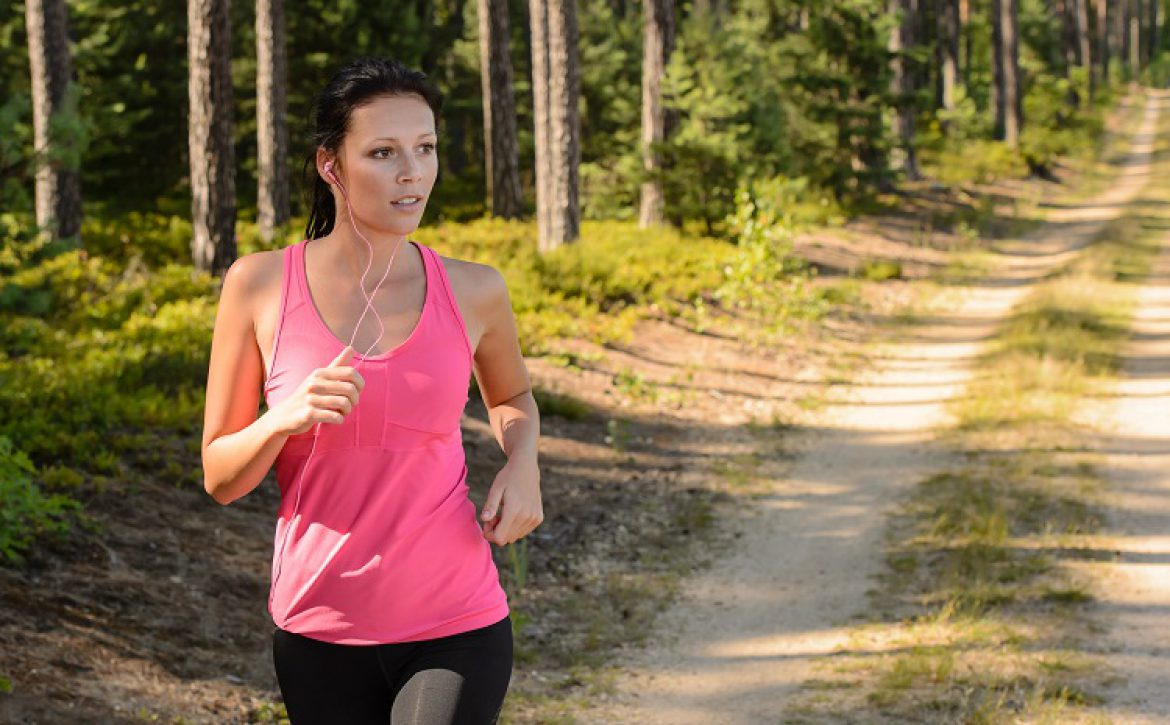 Woman running through forest outdoor training