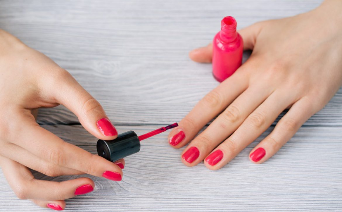 Female hands painted nails with red lacquer